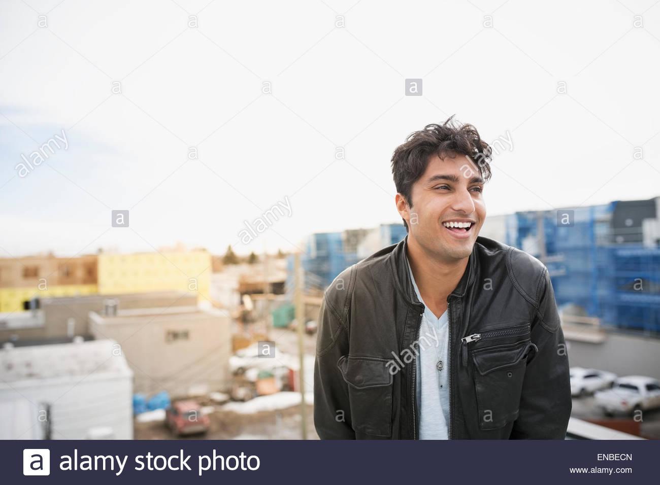 Lachender Mann auf städtischen Dach Stockbild