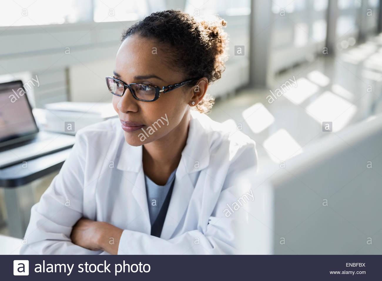 Nachdenkliche Wissenschaftler am Computer wegschauen Stockbild