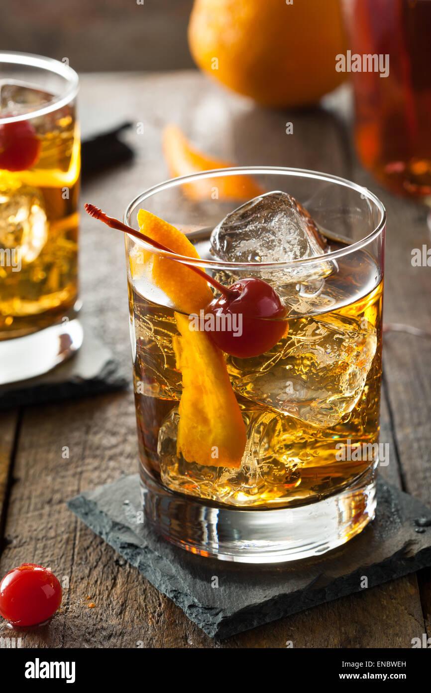 Hausgemachte Old Fashioned Cocktail mit Kirschen und Orangenschale Stockfoto