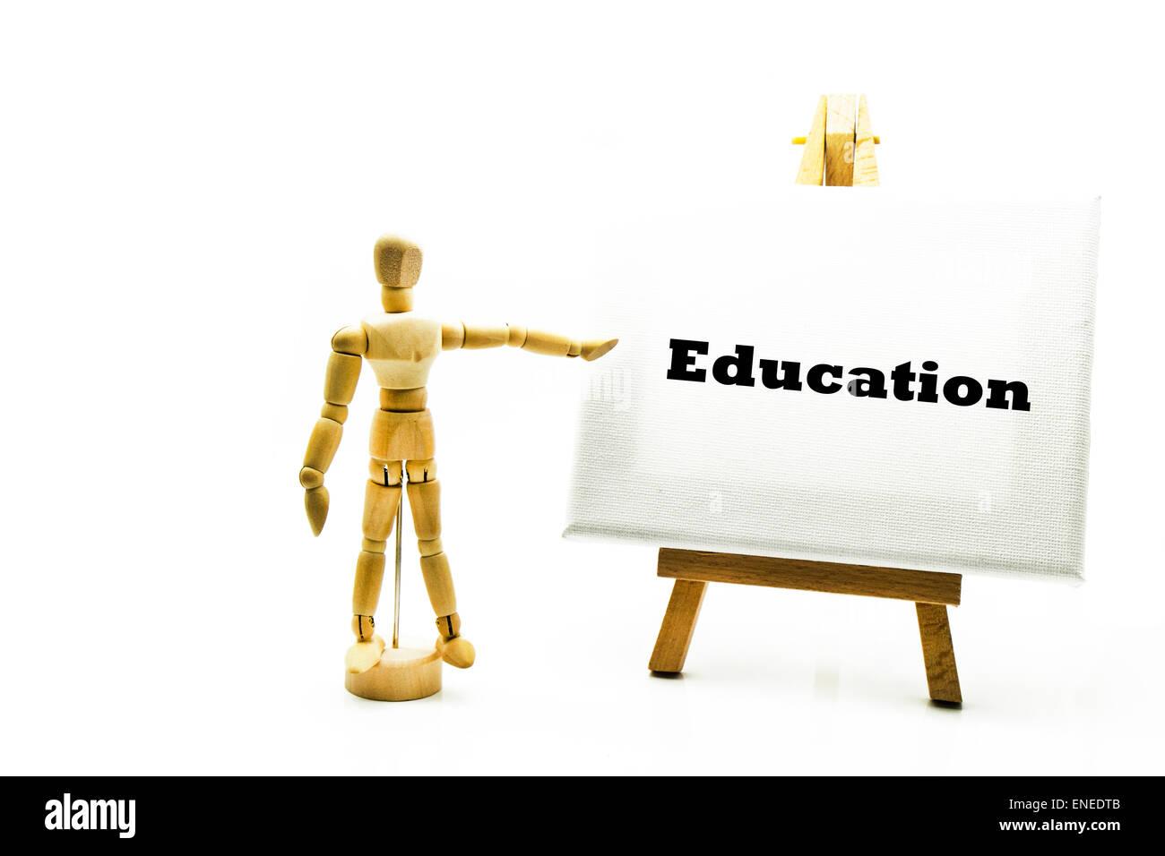 Hölzerne Mann mit weißen Tafel zeigt auf Wort Bildung Schule unterrichten zukünftige Universitätsschulen Stockbild
