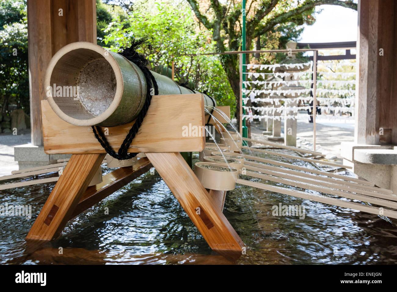 Japan, Nishinomiya-Schrein. Nahaufnahme von der Hauptleitung, die das Wasser in der Chozuya Wasser Reinigung Schriftart Stockfoto