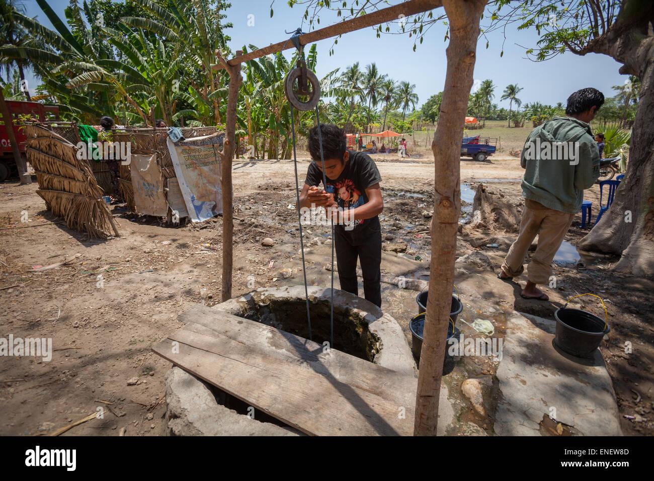 Ein Dorfbewohner heben Wasser aus einem kommunalen Wasser auch während der Trockenzeit in Insel Sumba, Indonesien. Stockbild