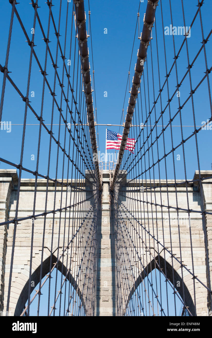 New York, New York State, Vereinigten Staaten von Amerika.  Brooklyn Bridge mit der amerikanischen Flagge fliegen Stockbild