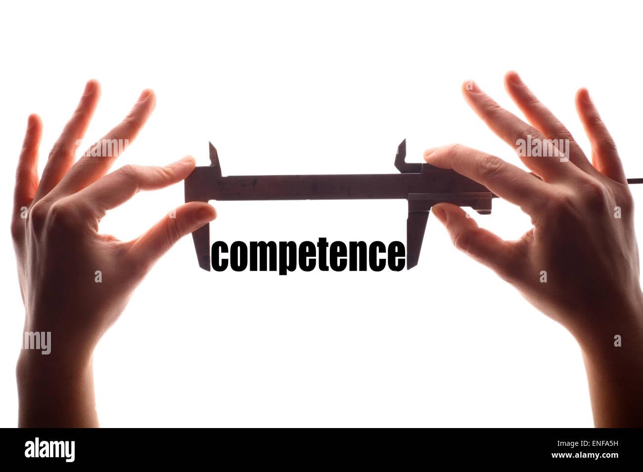 """Farbe der horizontalen Schuss von zwei Hände halten ein Bremssattel und messen das Wort """"Kompetenz"""". Stockbild"""