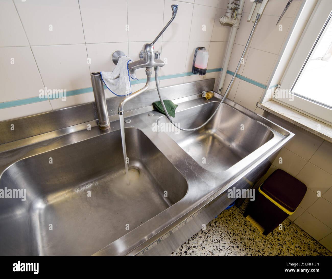 Großes Spülbecken aus Edelstahl Großküche mit Wasserhahn öffnen Stockfoto