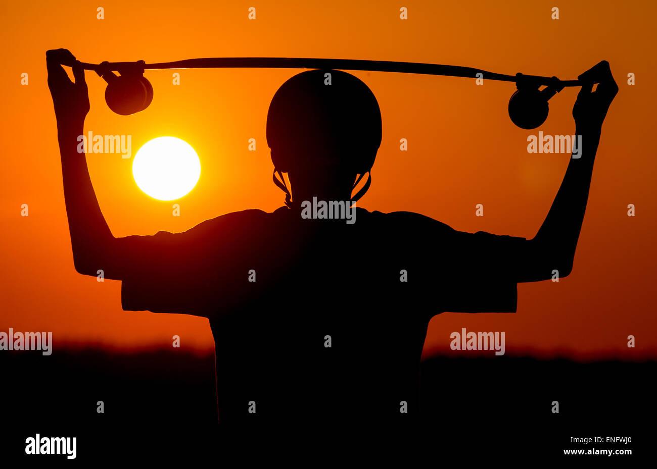 ILLUSTRATION - ein Junge und seine Longboard bei Sonnenuntergang auf einem Radweg in der Nähe von Sieversdorf Stockbild