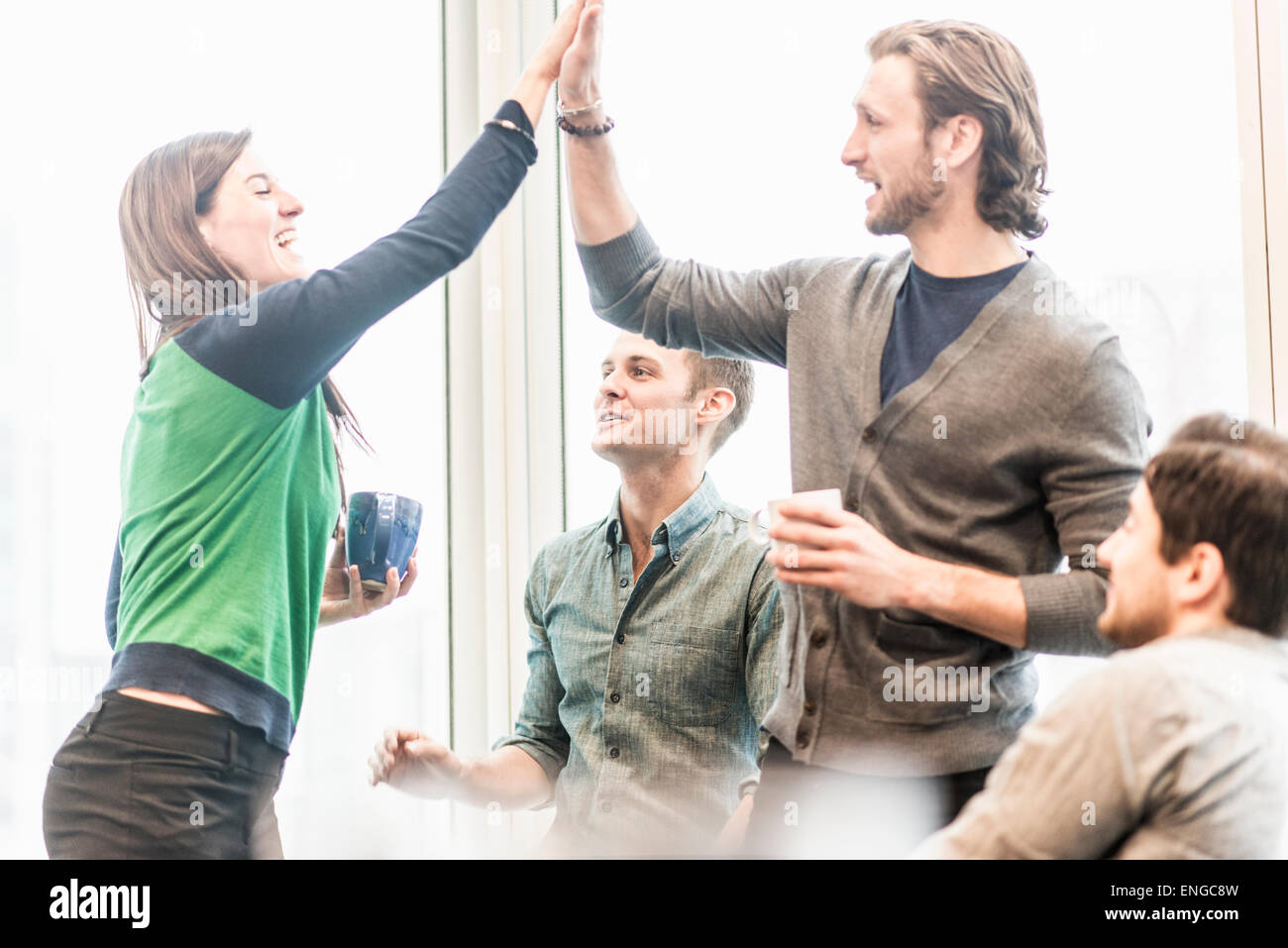 Vier arbeiten Kolleginnen und Kollegen auf eine Pause, lachen und teilen eine hohe fünf Geste. Stockbild