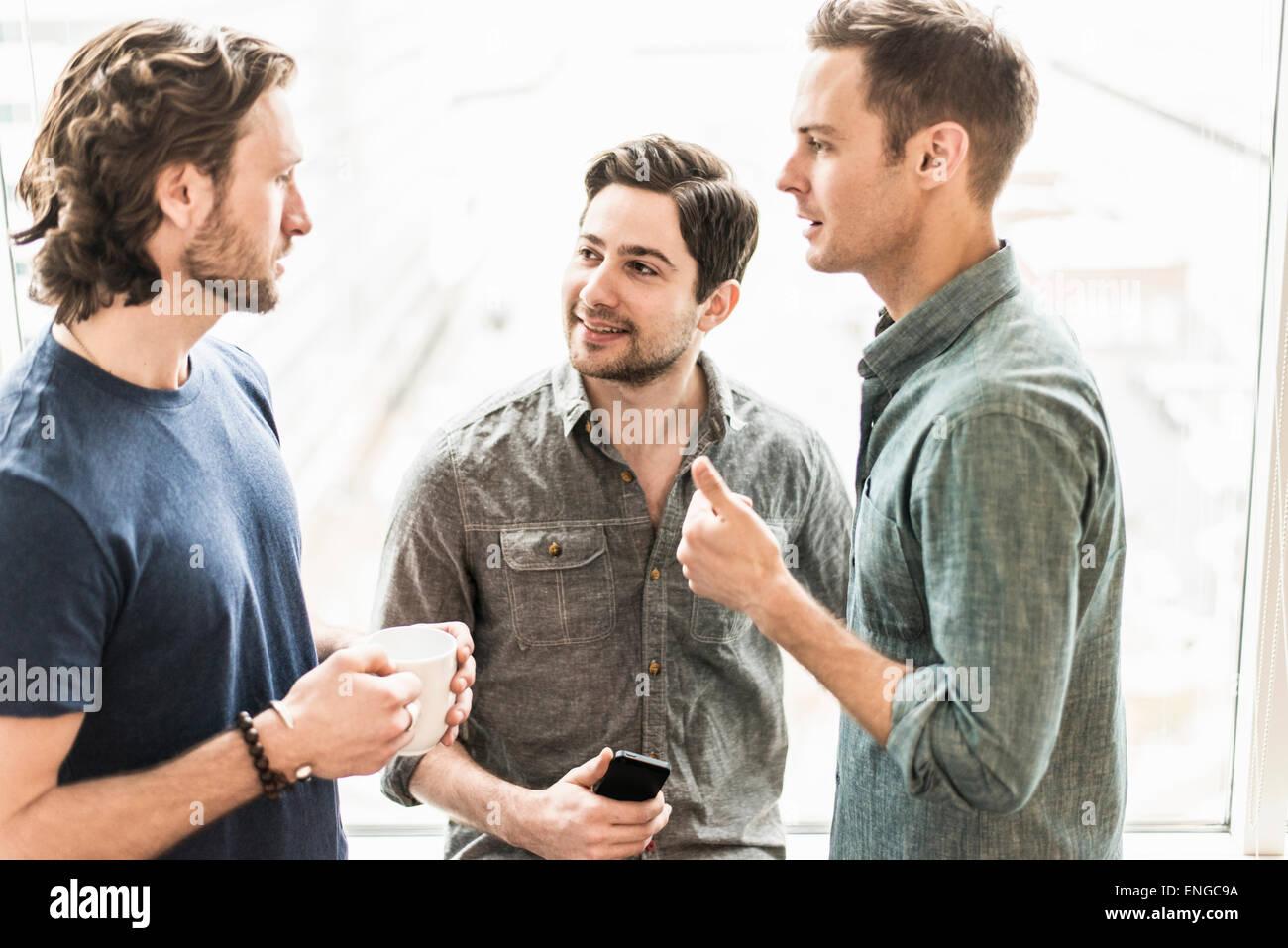 Drei Männer stehen, reden, mit einer Tasse Kaffee, einer mit einem Smartphone. Stockbild