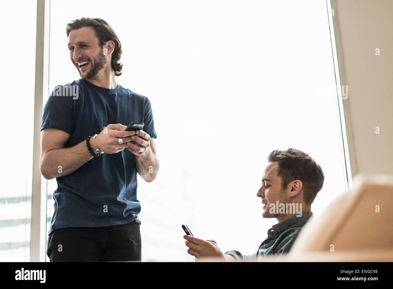 Zwei Männer in einem Büro, überprüfen ihre Smartphones. Ein aussehende Weg lachen. Stockfoto