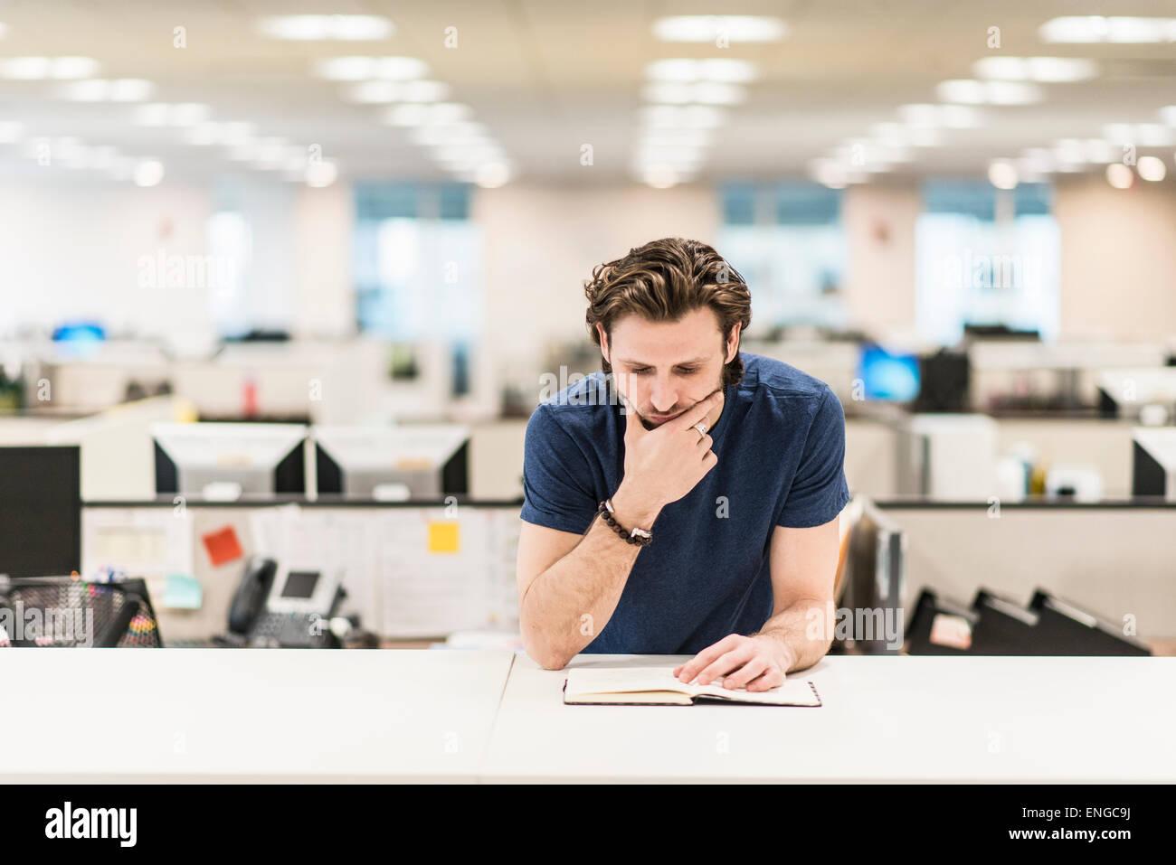 Ein Mann stützte sich auf seine Ellbogen und mit Blick auf ein offenes Buch auf einem Schreibtisch. Stockbild