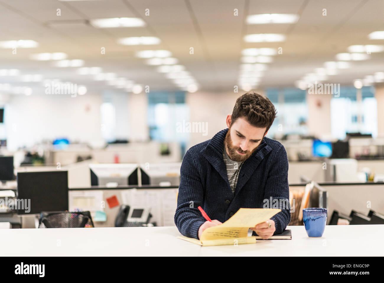 Ein Mann sitzt an einem Schreibtisch in einem Büro mit einem roten Stift schreiben. Stockbild