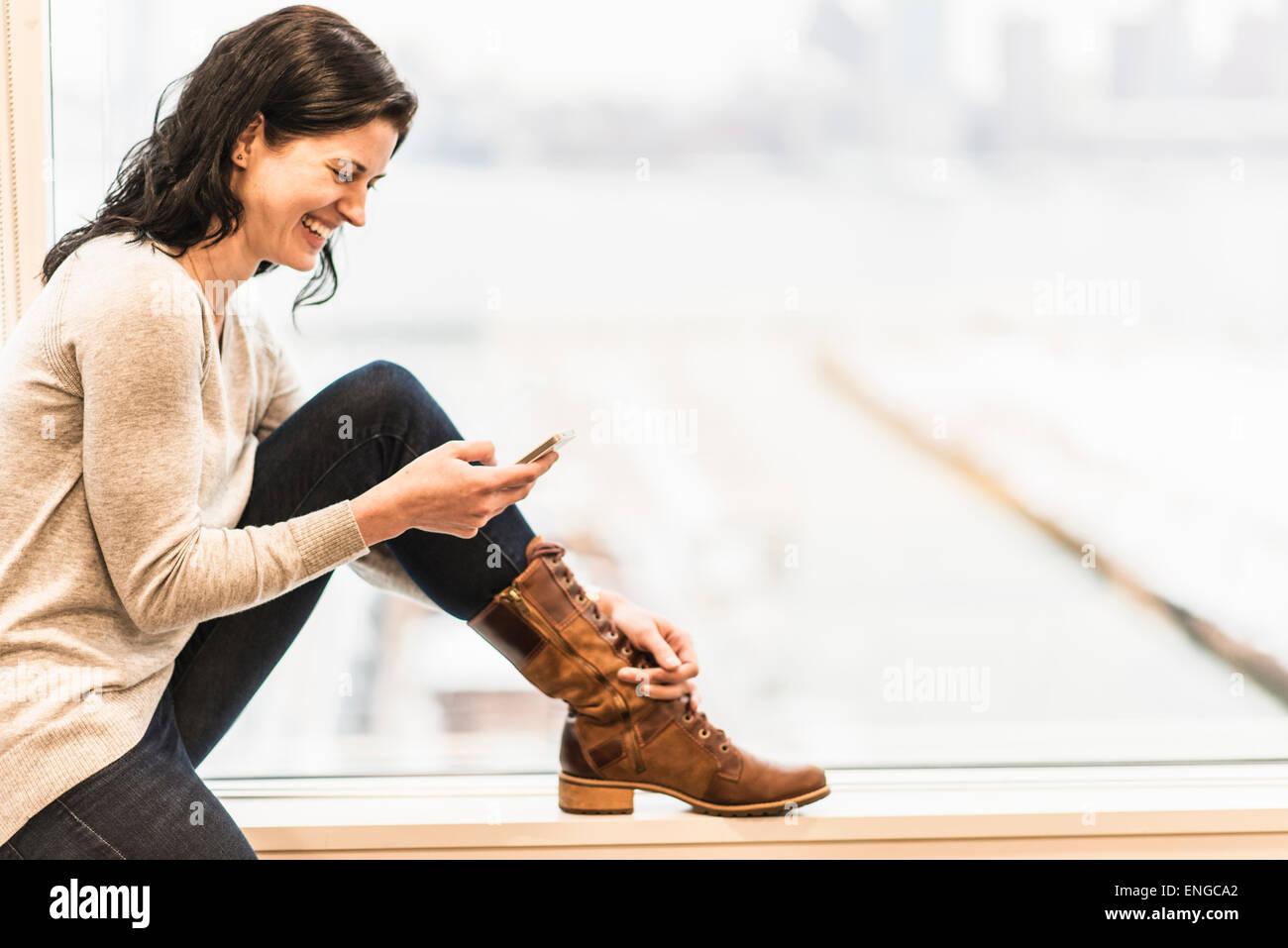 Eine Business-Frau sitzt an einem Fenster mit ihrem Smartphone. Stockbild
