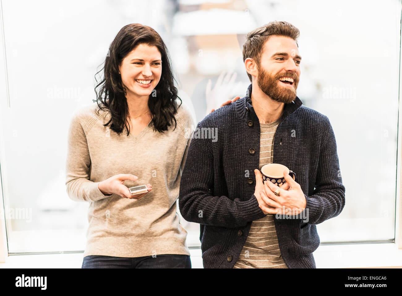 Eine Business-Frau sitzt an einem Fenster hält ein smart Phone, Gespräch mit einem Mann hält eine Stockbild