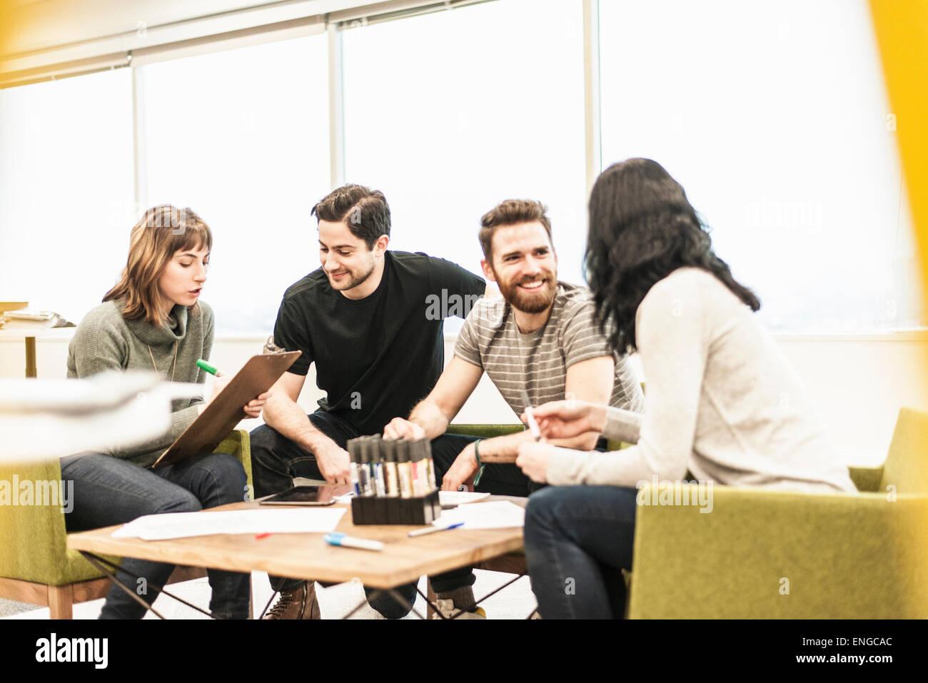 Vier Personen sitzen an einem Tisch mit Kollegen bei einer Planungsbesprechung holding Farbstiften und arbeiten Stockfoto