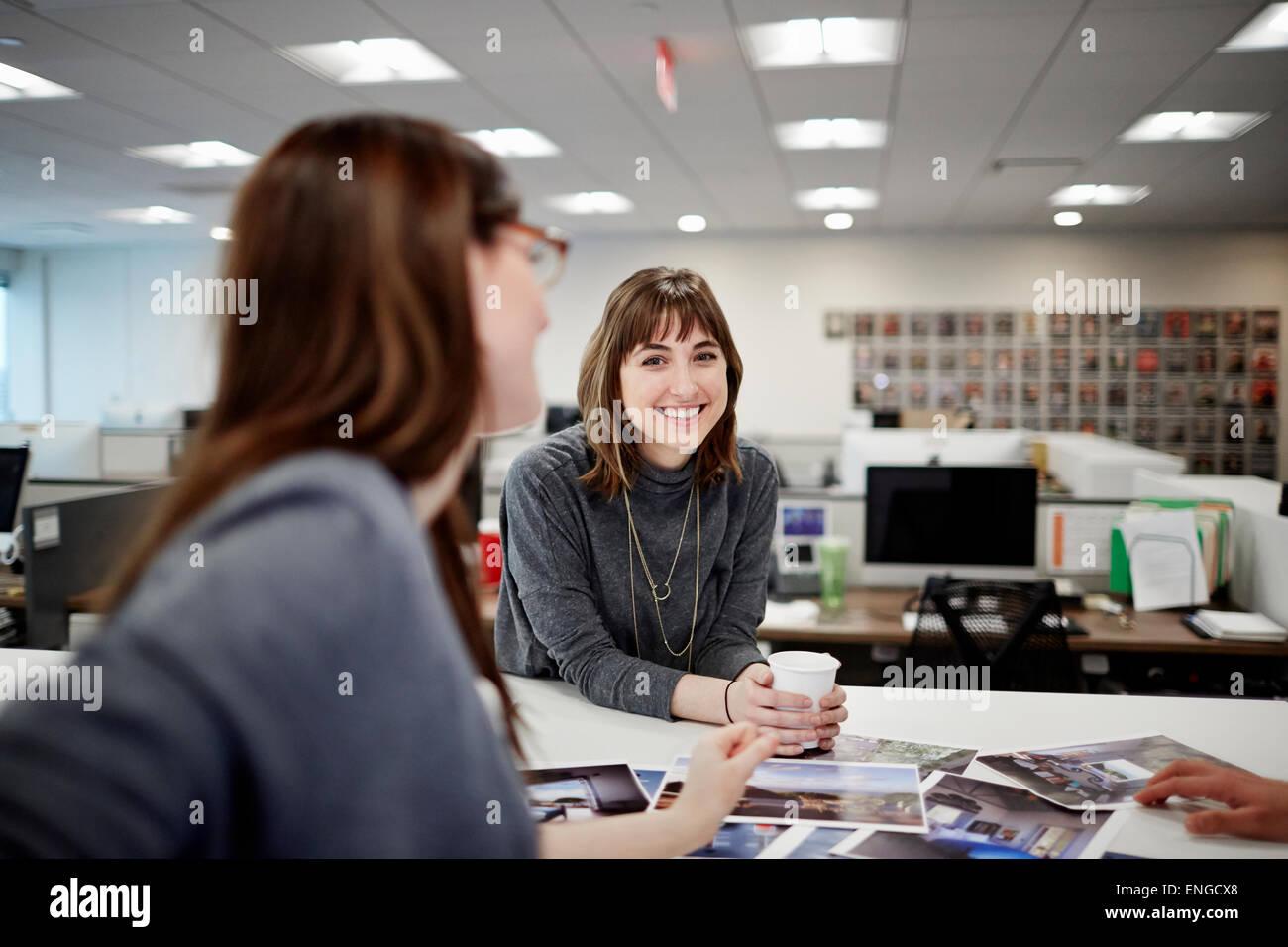 Zwei Frauen sitzen in einem Büro reden und lachen. Stockbild