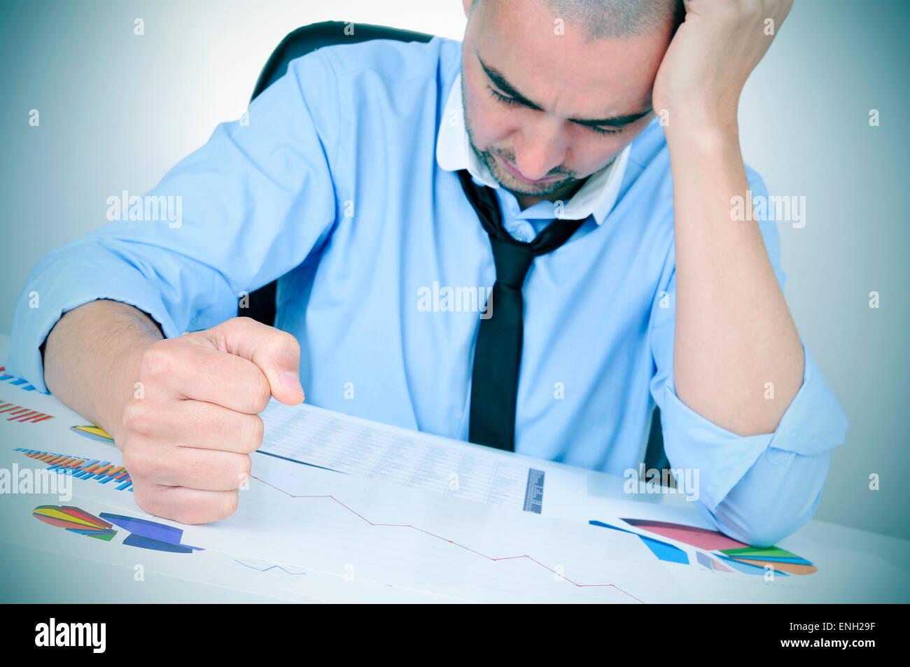 ein junger kaukasischer Geschäftsmann in seinem Büroschreibtisch voller Grafiken und Diagramme beobachten Stockbild