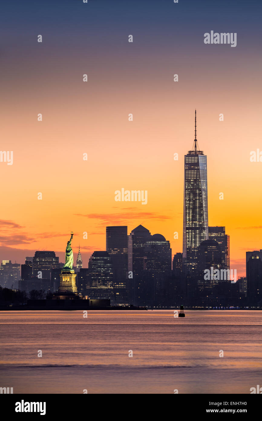 Lower Manhattan mit Freedom Tower und The Statue of Liberty bei Sonnenaufgang Stockbild