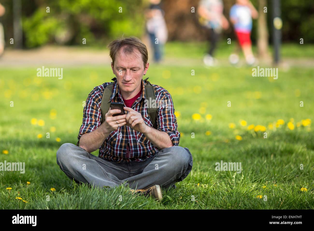 Junger Mann mit Smartphone sitzen auf dem Rasen in einer Stadt Park. Stockbild