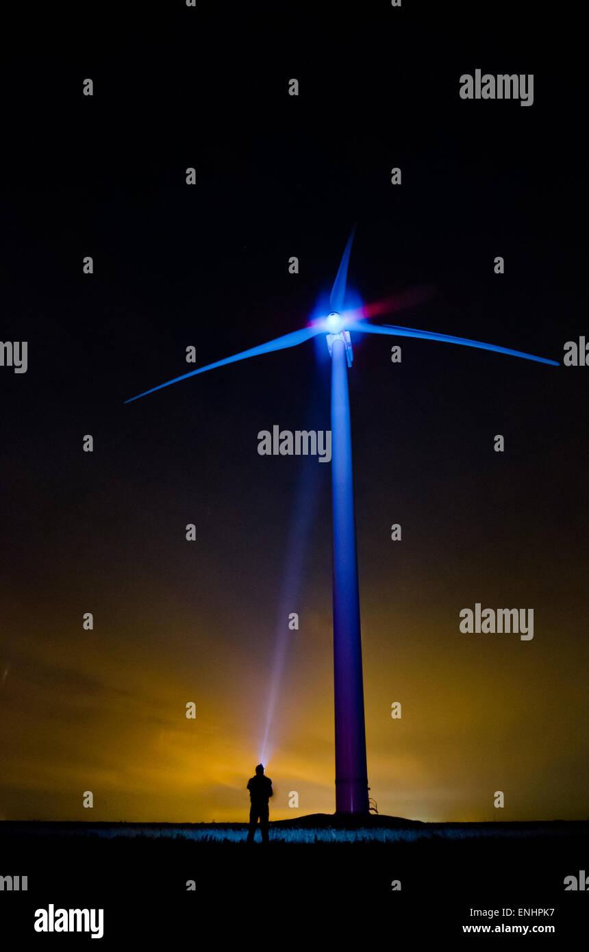Die Windkraftanlage in einem ungewöhnlichen Licht-ein einsamer Mann nachts erstrahlt Schraube mit Taschenlampe. Stockbild