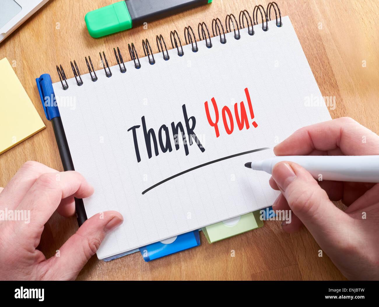 Ein Geschäftsmann schreiben die Worte, ich danke Ihnen, auf einen Notizblock. Stockbild