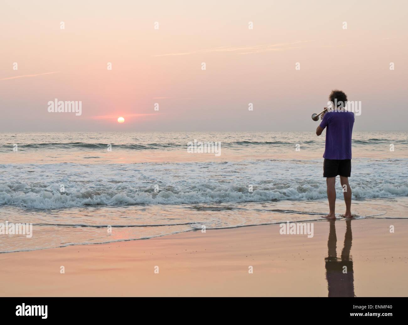Ein Mann, eine Trompete auf Agonda Beach Goa in Indien bei Sonnenuntergang Stockfoto