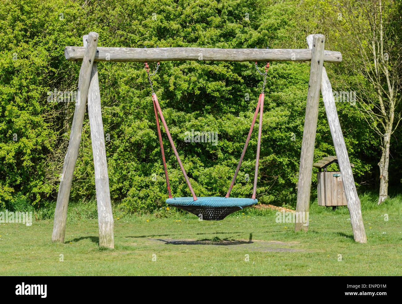 Moderner Swing mit Holzrahmen in einem Park. Stockbild