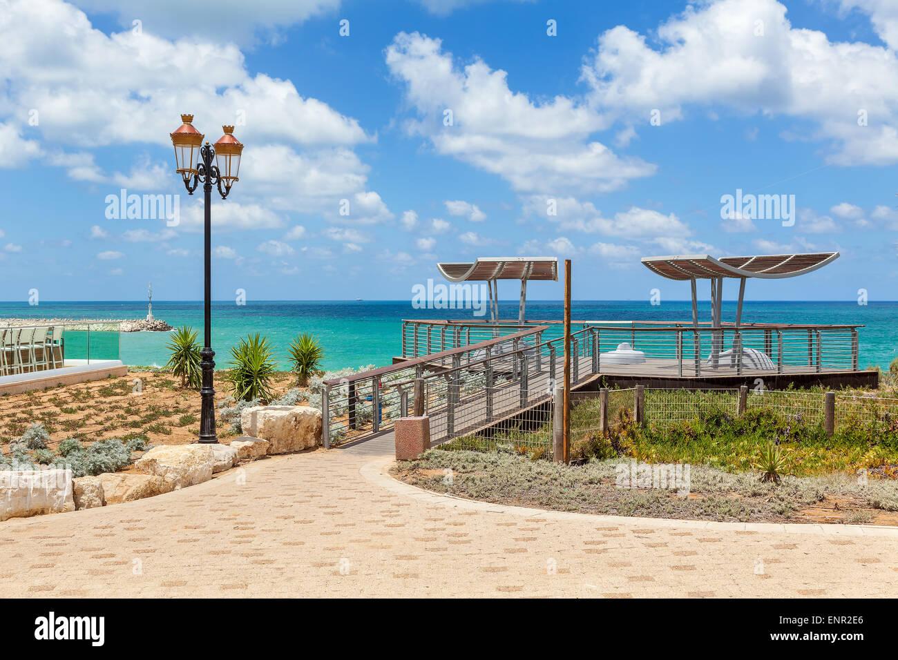 Sicht und Laternenpfahl auf Promenade mit Blick auf Mittelmeer unter blauem Himmel mit weißen Wolken in Ashkelon, Stockbild
