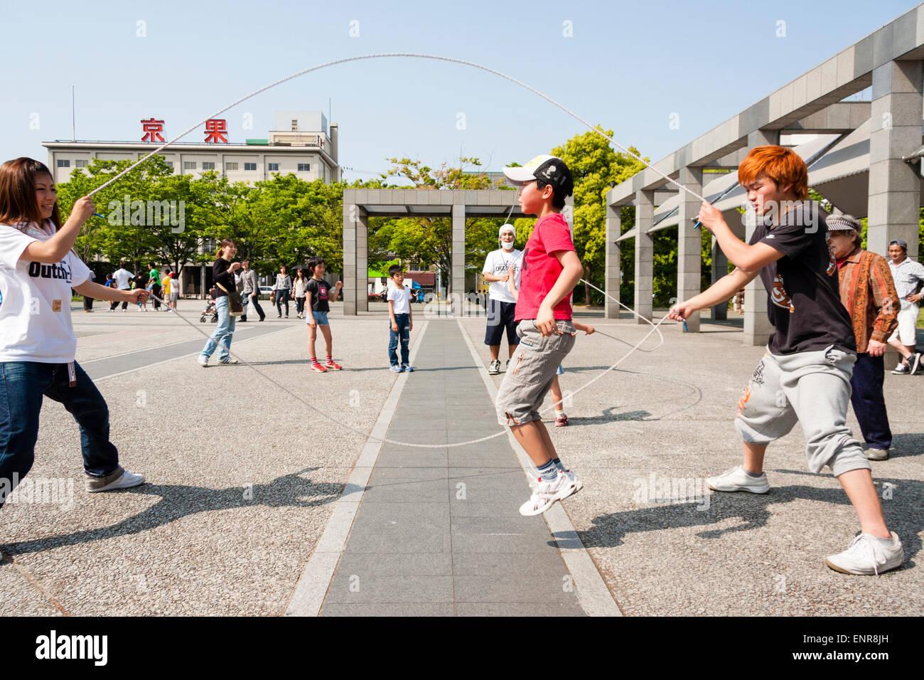 Japan, Kyoto. Kleiner Junge überspringen überspringen Wettbewerb mit Ende überspringen Seil und orange Stockbild