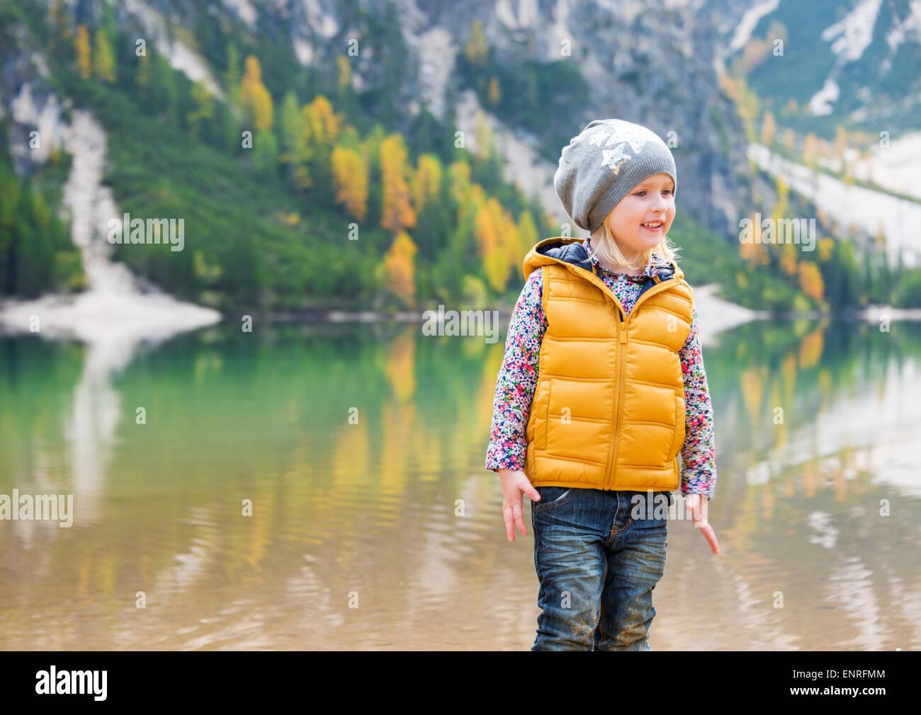Eine lächelnde blonde Mädchen trägt einen Hut steht am Ufer des Sees Bries. Hinter ihr, die Berge Stockbild