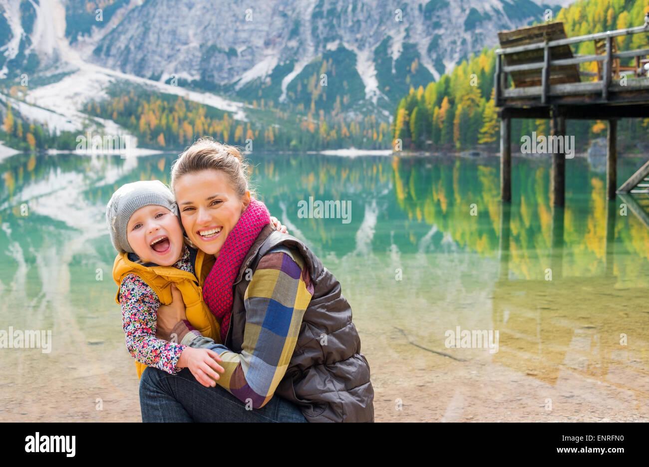 Knienden Mutter und stehende Kind tragen Outdoor-Ausrüstung sind kuscheln, Lächeln und Lachen am Ufer Stockbild