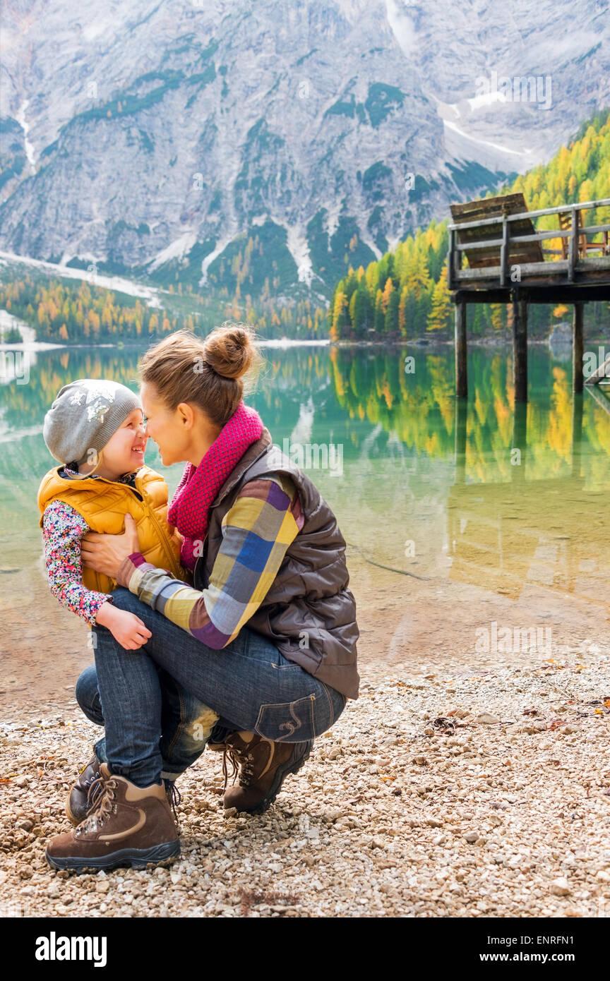 Eine kniende Mutter und stehende Kind trägt Outdoor-Ausrüstung geben Eskimo Küsse an den Ufern des Stockbild