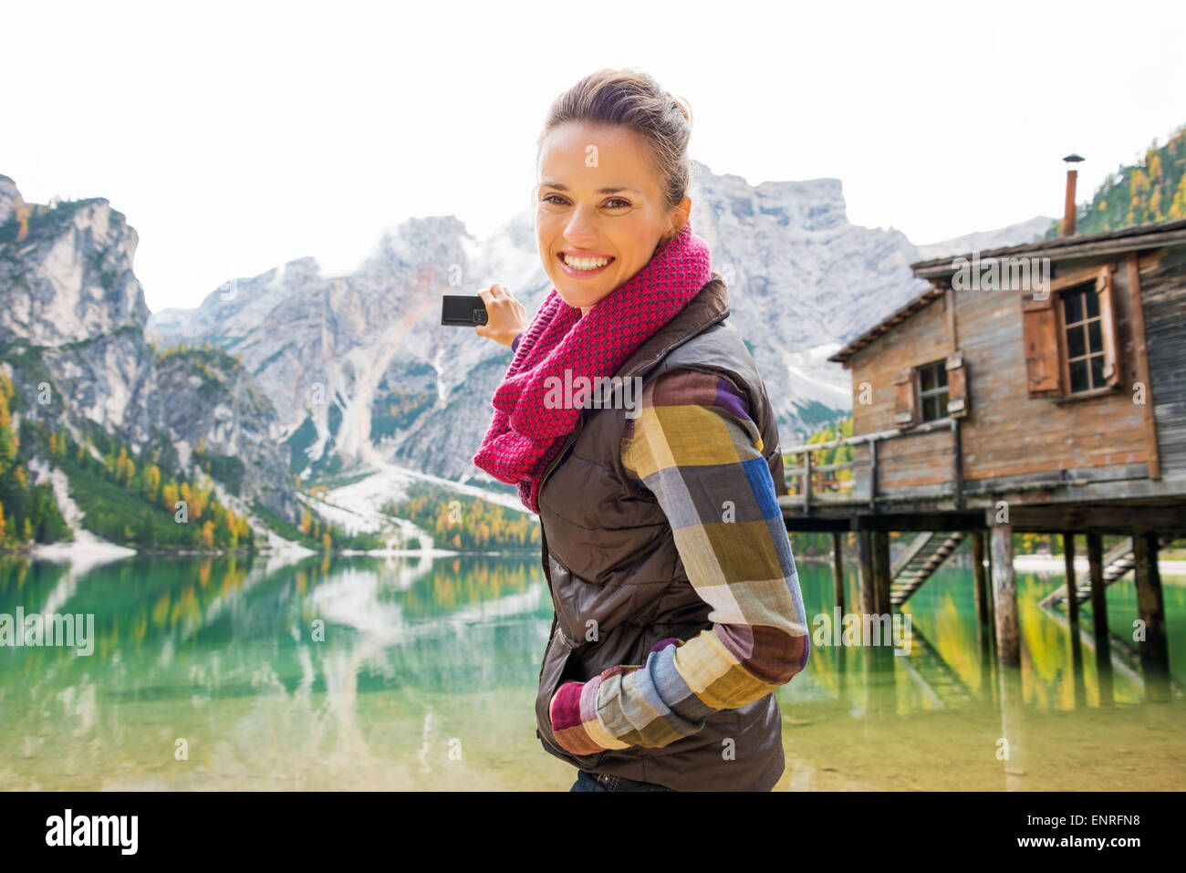Eine lächelnde Brünette in Outdoor-Ausrüstung ist mit dem Ziel, ihrer Digitalkamera heraus am See Stockbild
