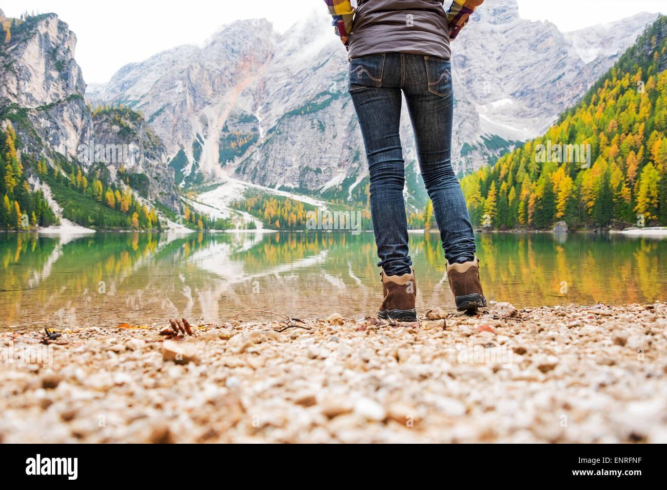 Studium der unteren Hälfte. Eine Frau Wanderer steht am Rande des Sees Bries. Im Vordergrund, einen Kieselstrand. Stockbild