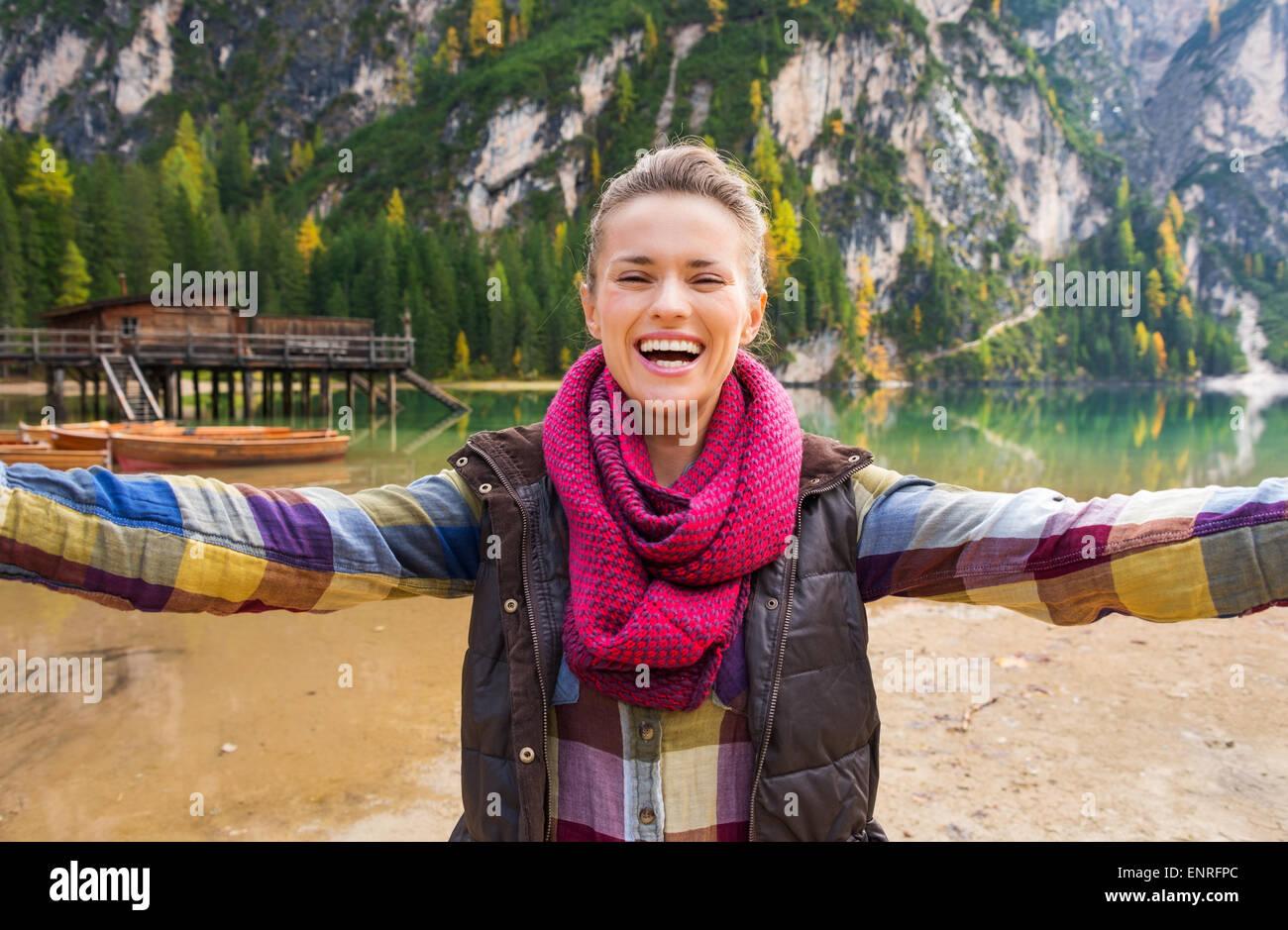 Eine Brünette tragen Outdoor-Ausrüstung ist Lachen und Lächeln während der Einnahme von Selfie. Stockbild