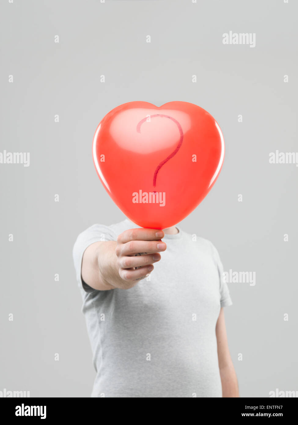 kaukasischen Mann hält Herz geformt Ballon mit Fragezeichen vor seinen Kopf vor grauem Hintergrund Stockfoto
