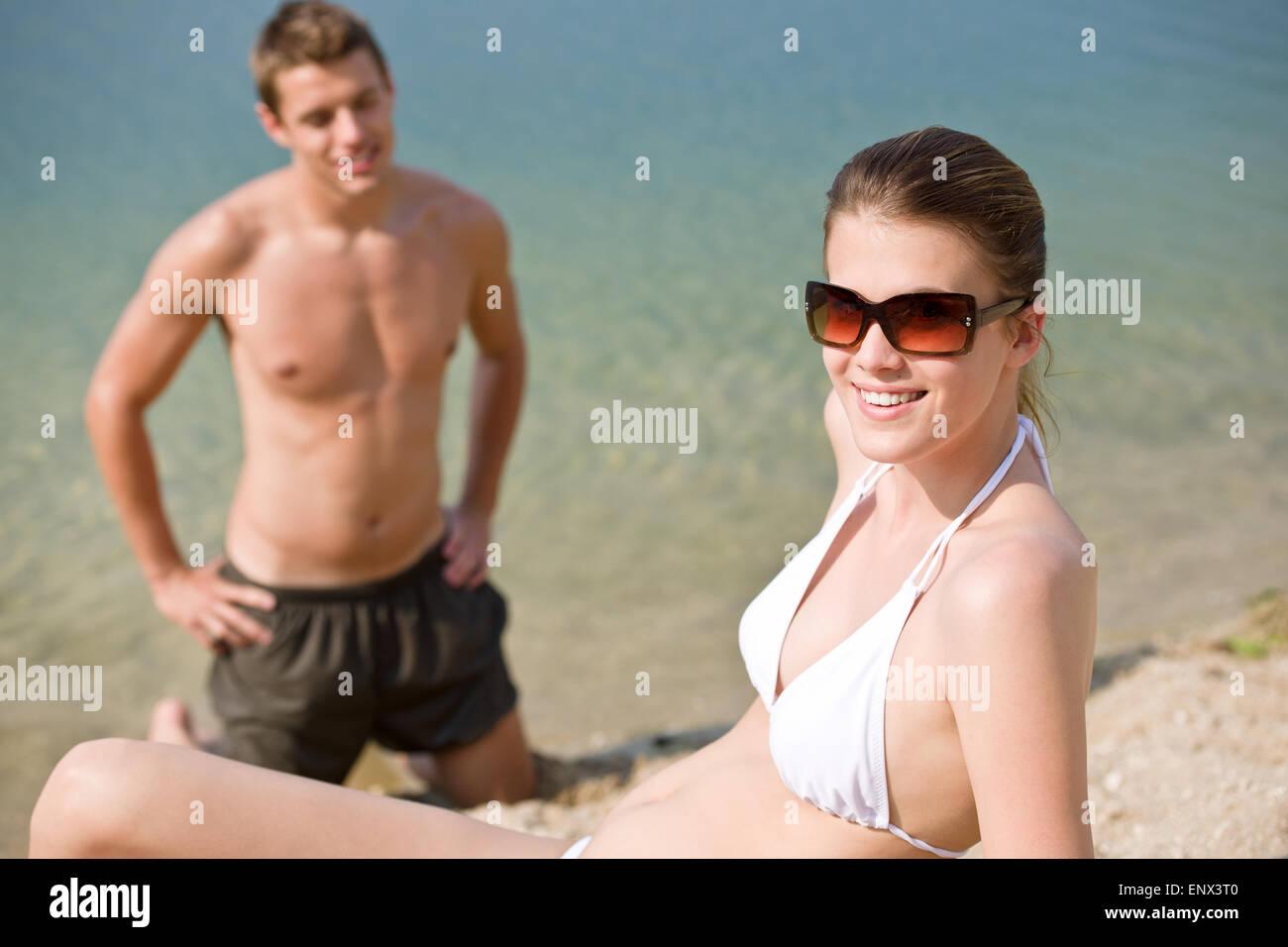 Paar am Strand - Frau im Bikini Sonnen Stockbild