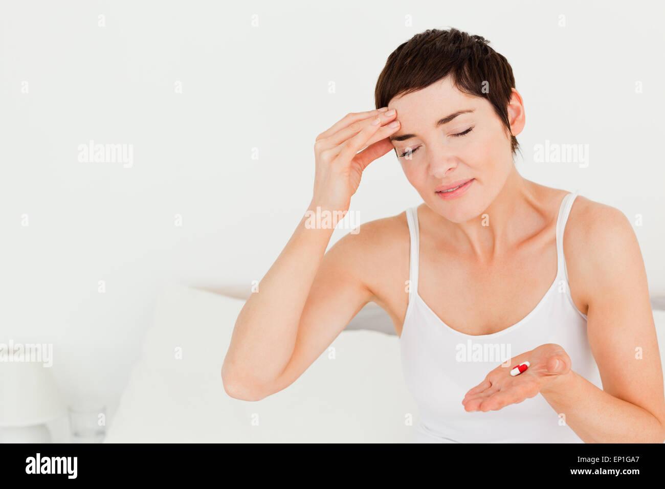 Niedliche Brünette mit Kopfschmerzen Stockbild