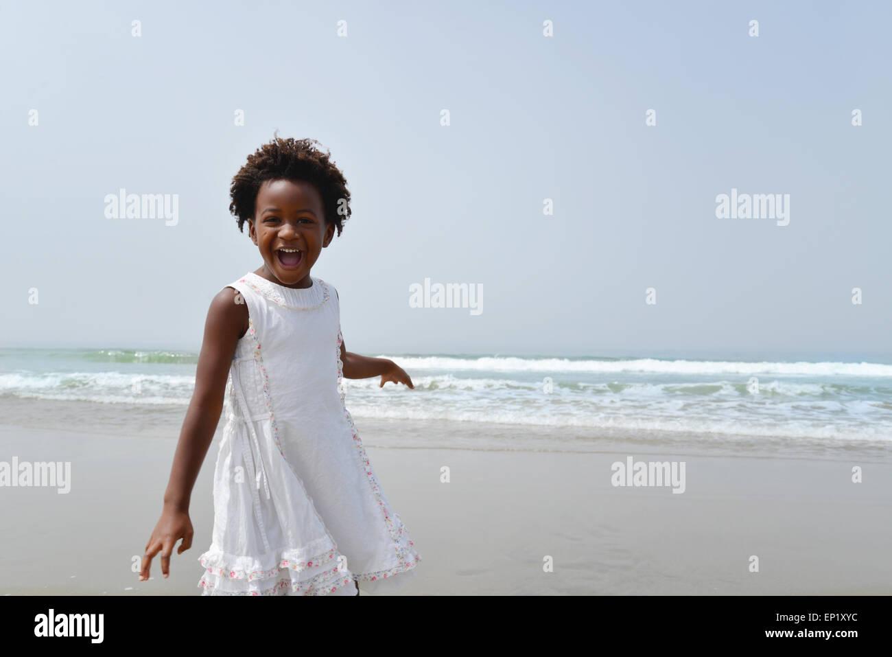 Porträt von einem glücklichen afroamerikanische Mädchen am Strand Stockbild