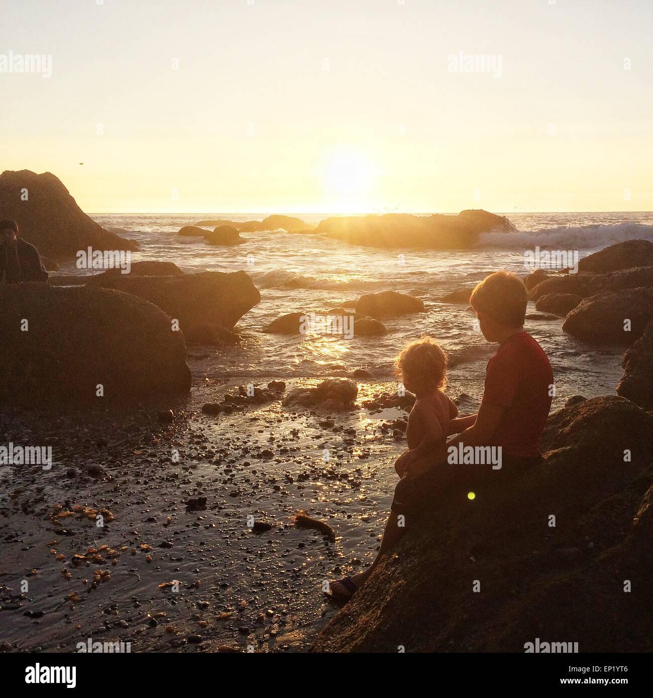 Zwei Jungs sitzen auf den Felsen am Strand bei Sonnenuntergang, Dana Point, Kalifornien, USA Stockbild