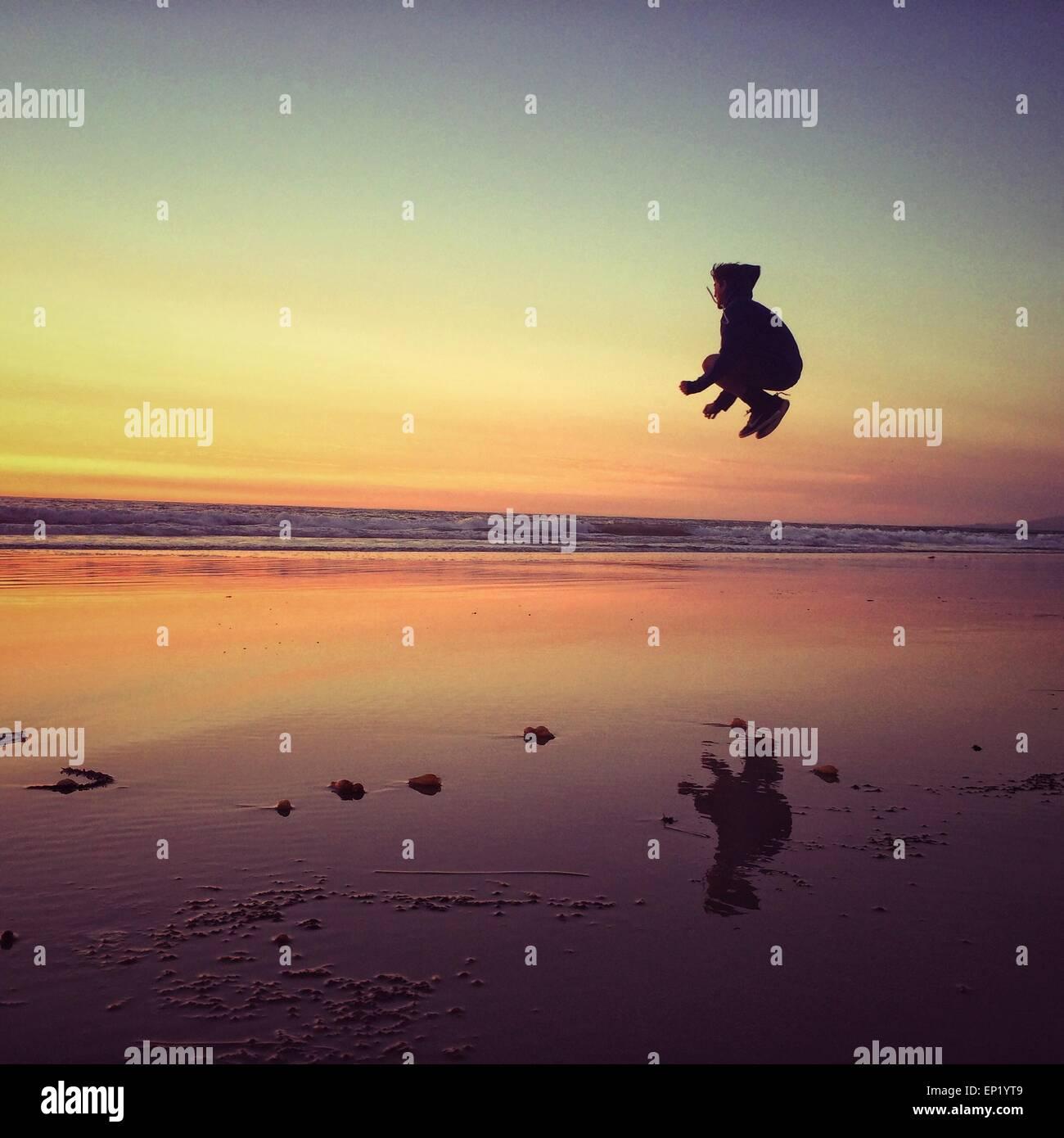 Junge am Strand springen Stockbild