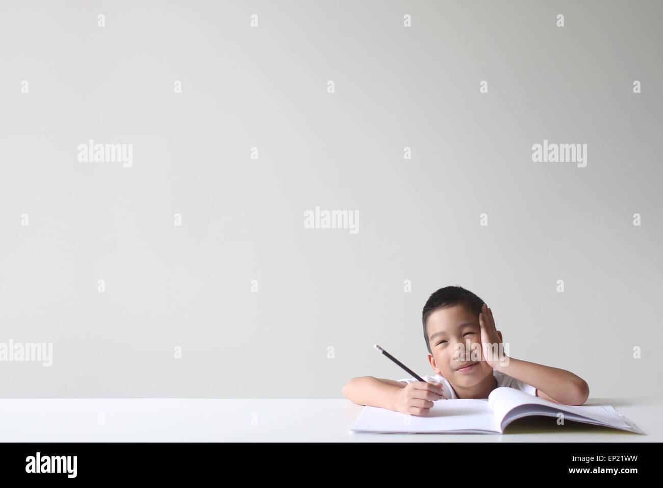 Junge sitzt auf einer Tabelle studieren Stockbild