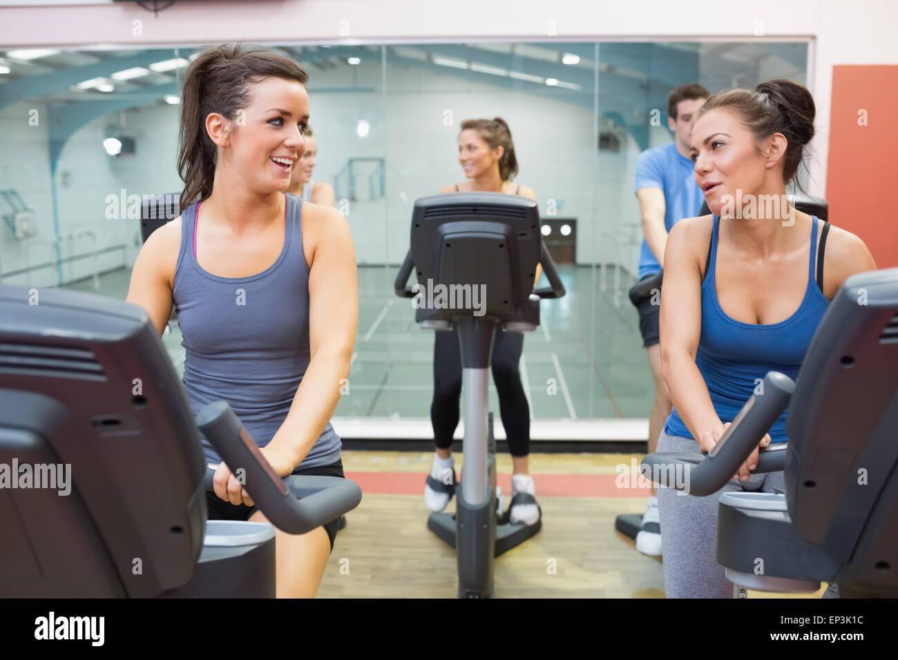 Zwei Frauen reden während des Trainings in einem Spinning Kurs Stockbild