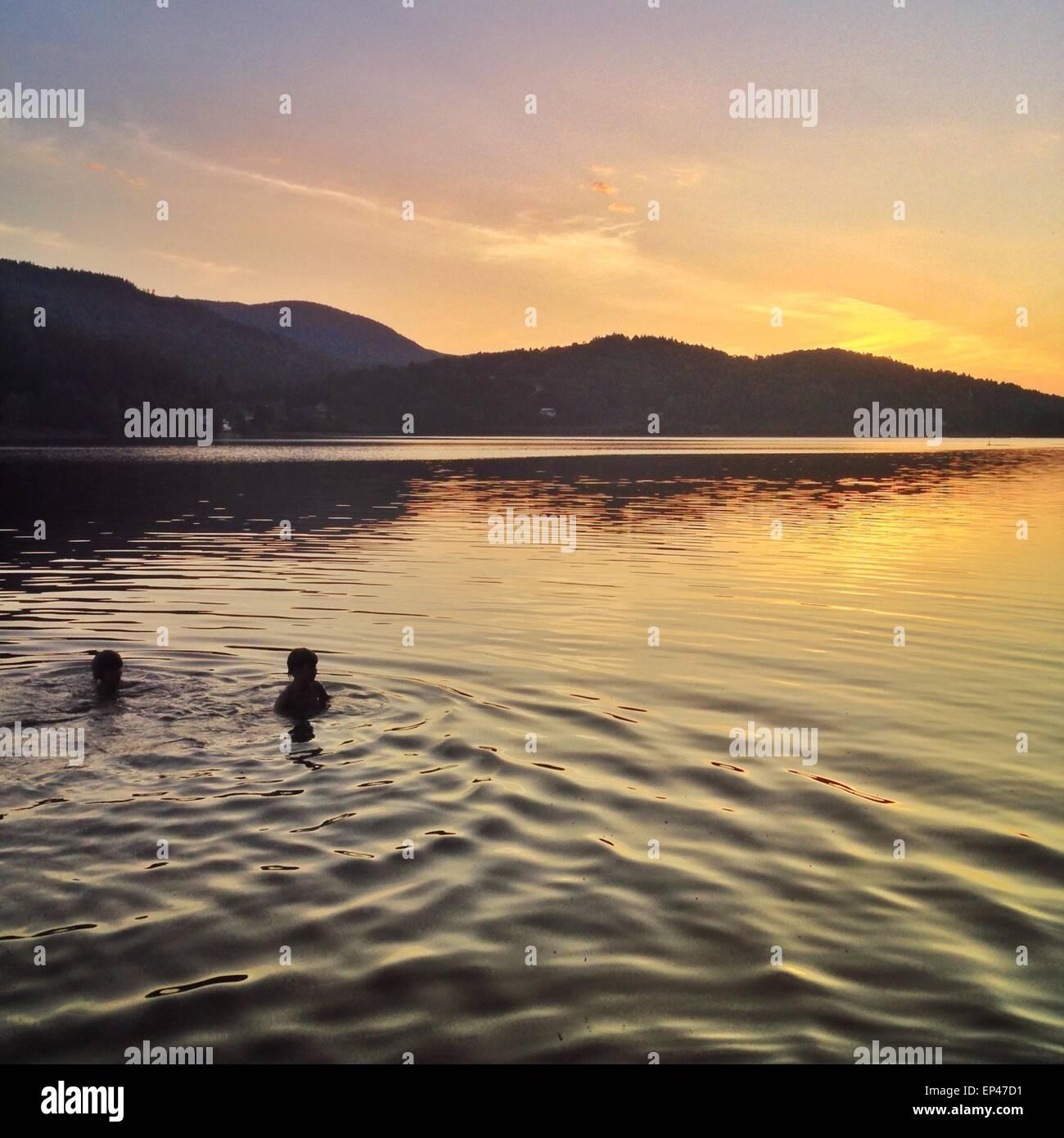 Zwei Jungen schwimmen im Meer bei Sonnenuntergang, Hof, Vestfold, Norwegen Stockbild