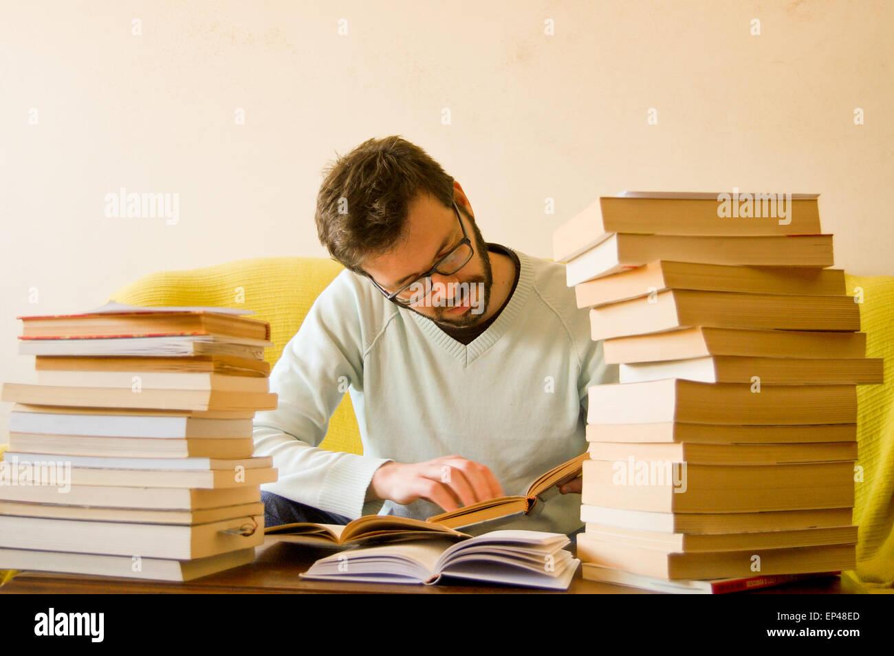 Mann mit einem Stapel Bücher vor, der ihn studieren Stockbild