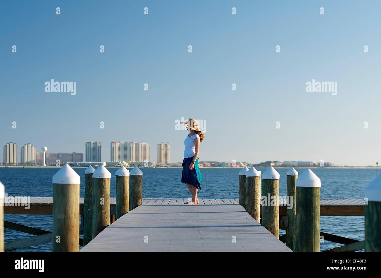 Frau in der Sonne Hut Stand am Ende ein Boot Dock, Florida, USA Stockbild