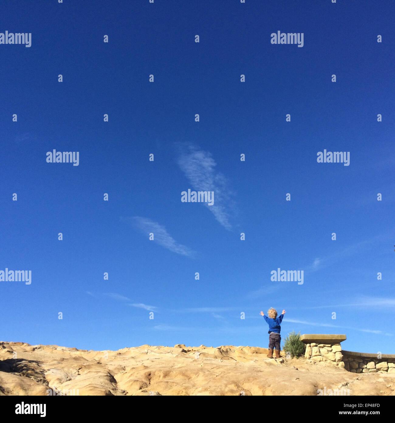 Junge stand mit seinen Armen in der Luft Stockbild