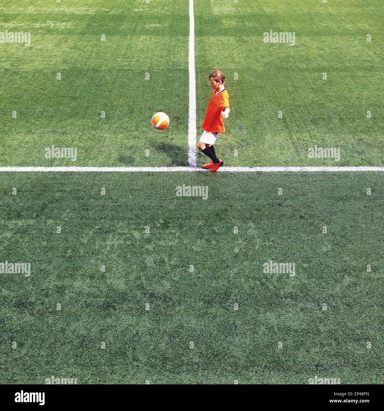 Seitenansicht eines jungen auf dem Fußballplatz Stockbild