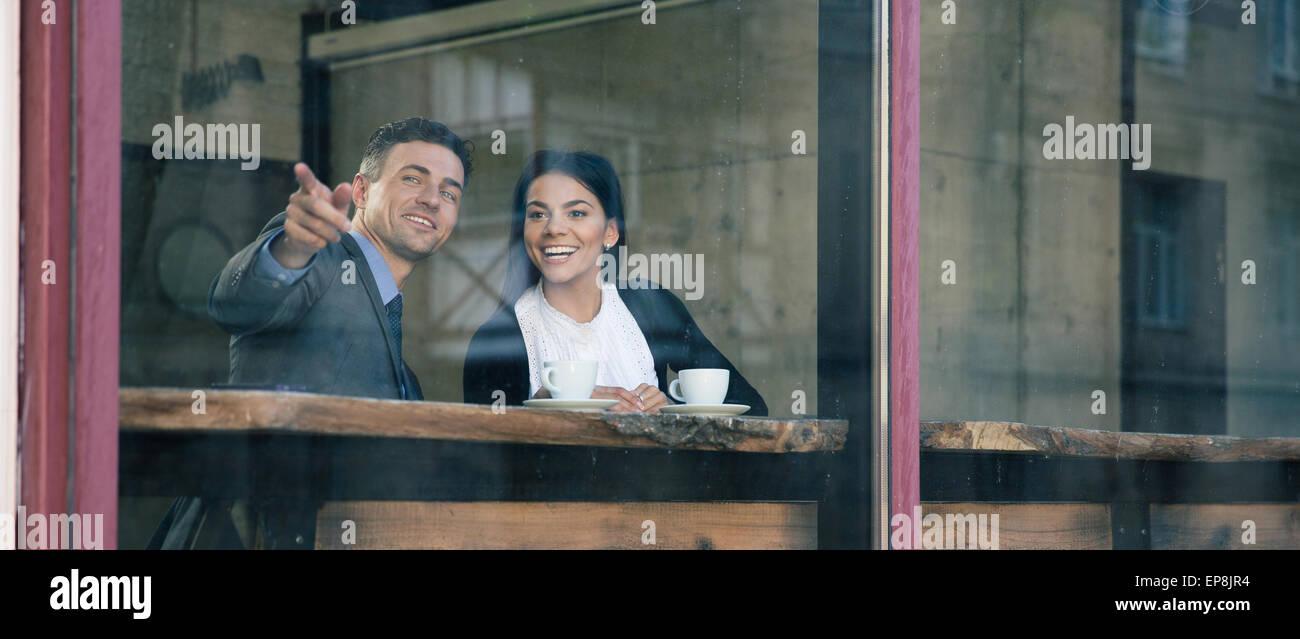 Glücklich Kaufmann verweist auf etwas im café Stockbild