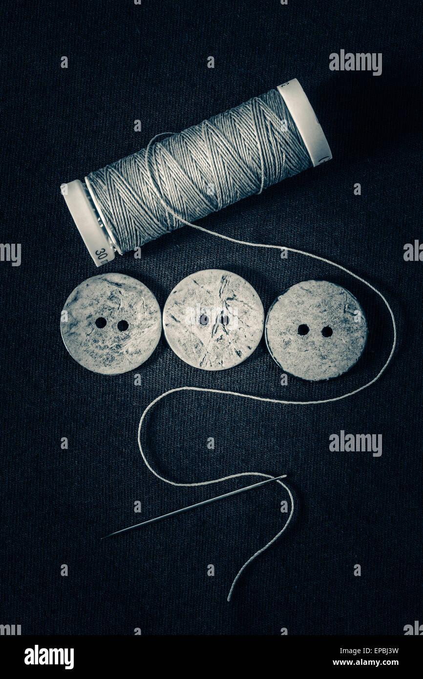 Knöpfe, Nadel und Faden Monochrom Stockbild