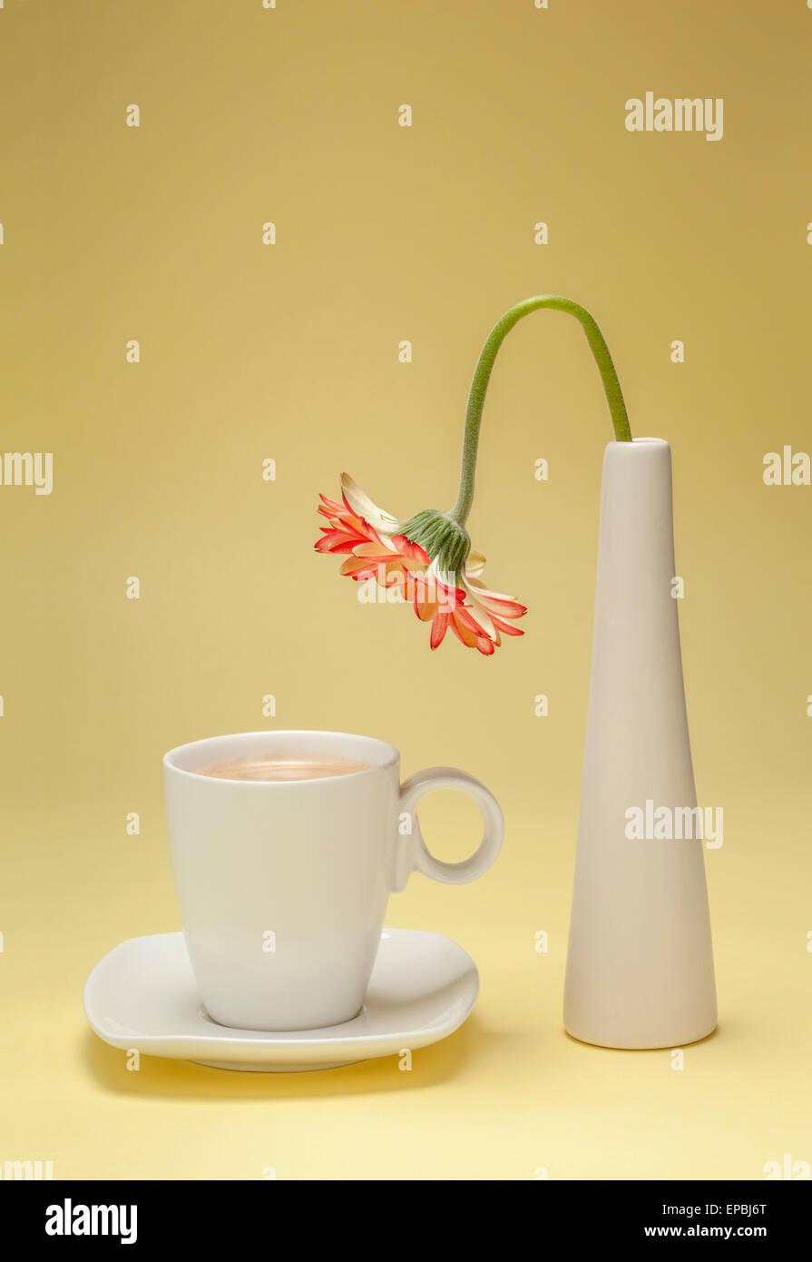Durstige Blume beugte sich über eine Tasse Kaffee Stockbild